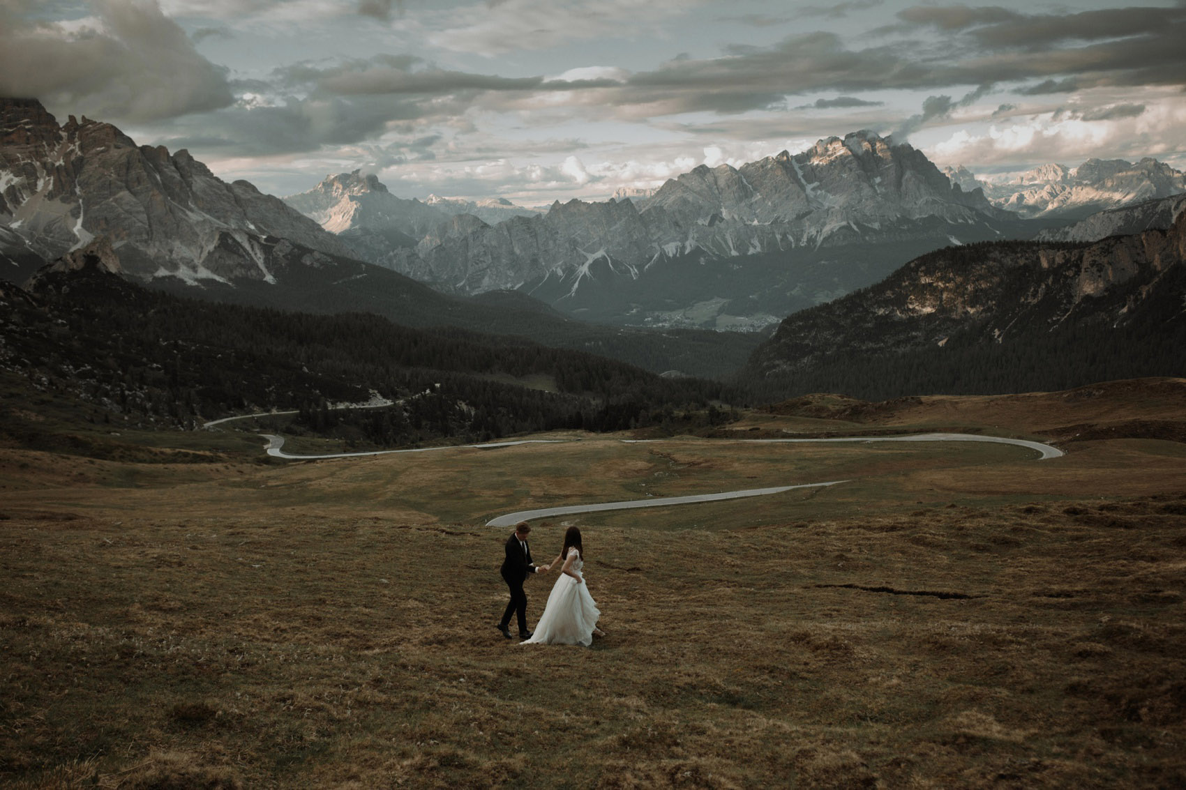 wide view couple walking with mountains on the background