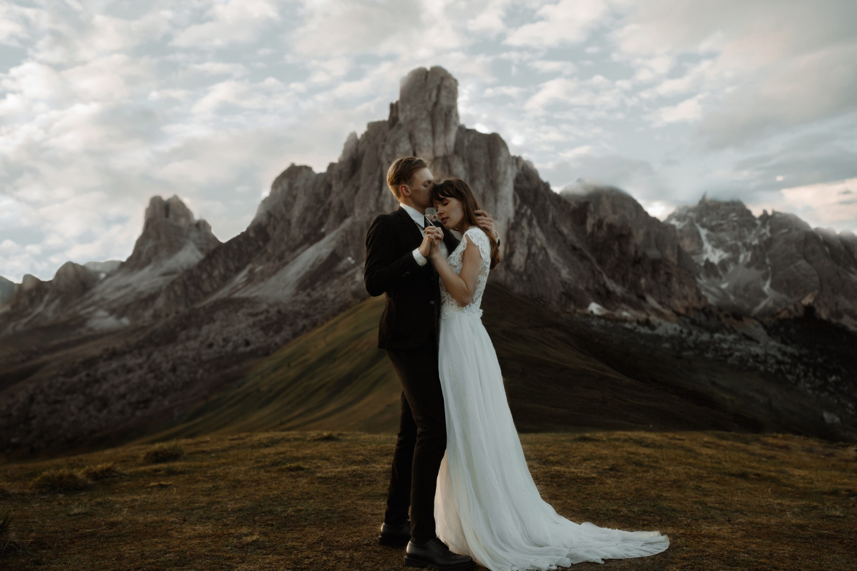 couple hugs with a mountain in the background