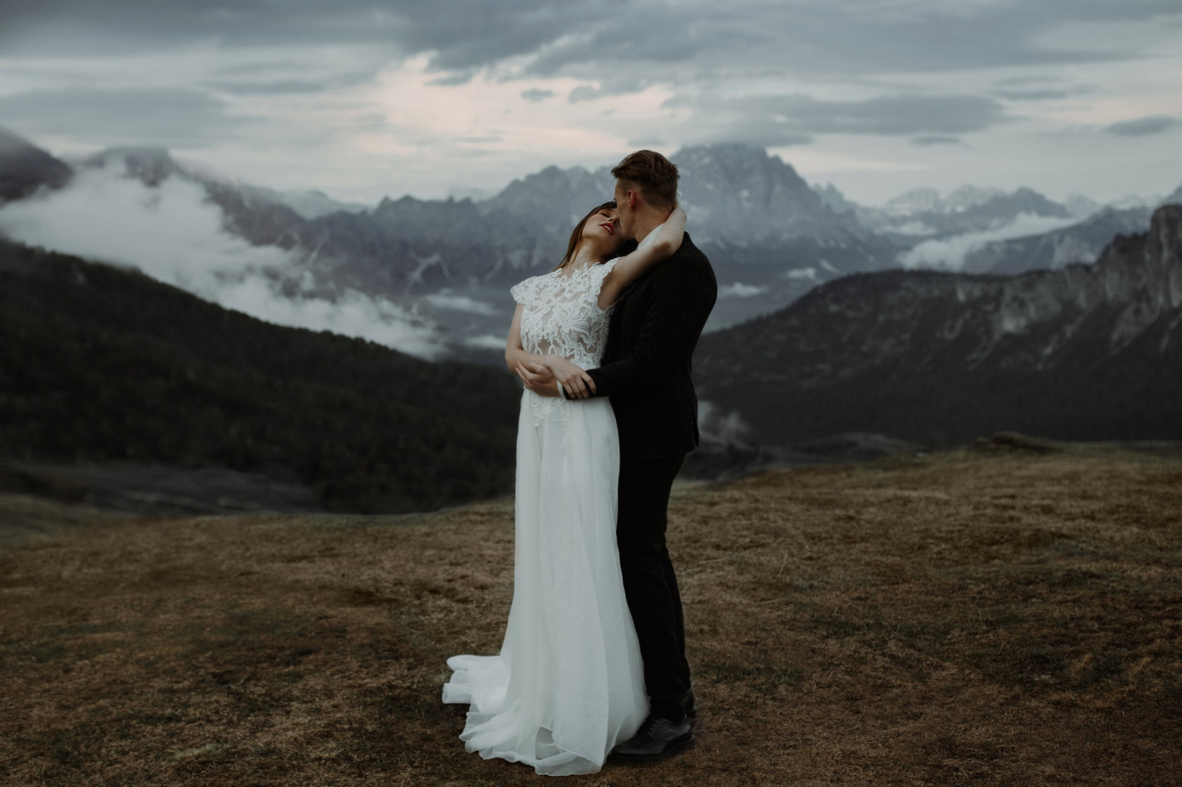 couple kissing with a mountain in the background