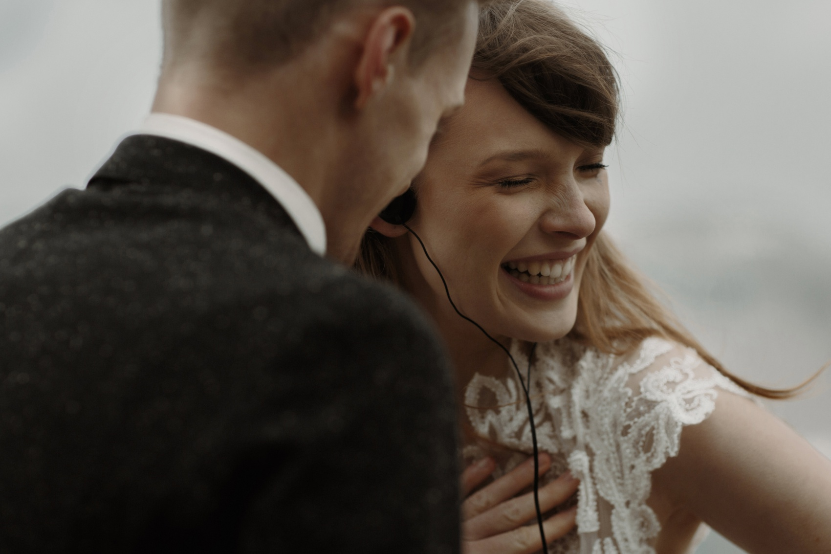 bride laughs with hand on her chest