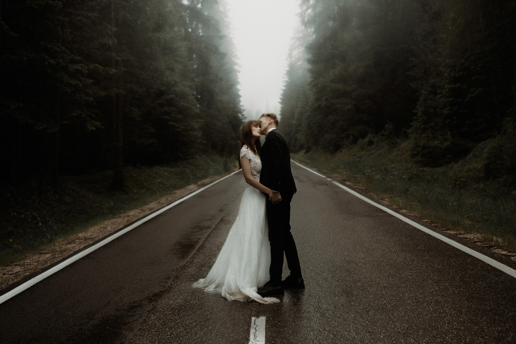 couple kissing in the middle of a road