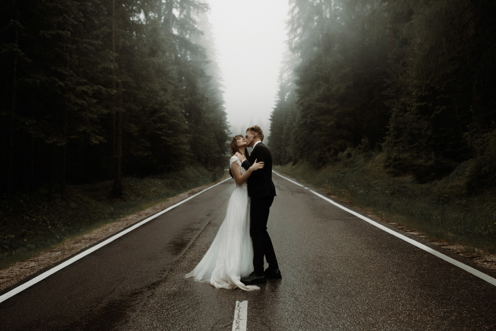 couple kissing at the centre of a road