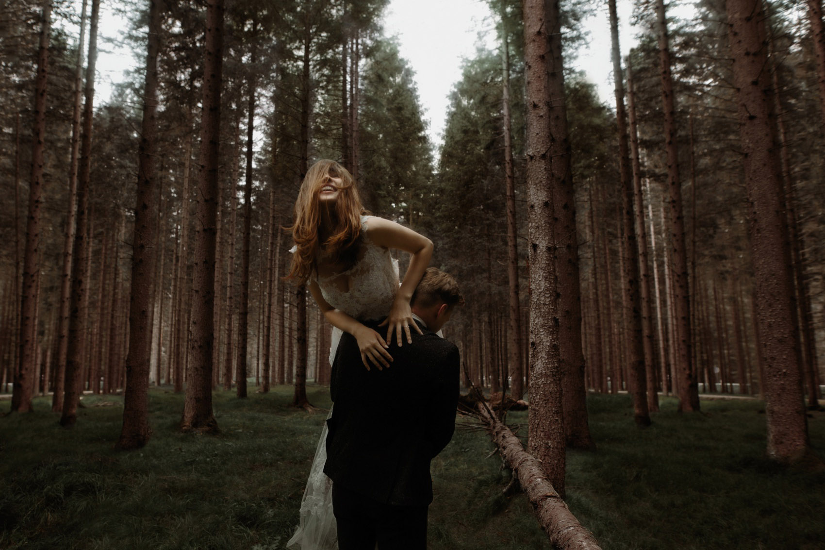 man carries woman in the forest