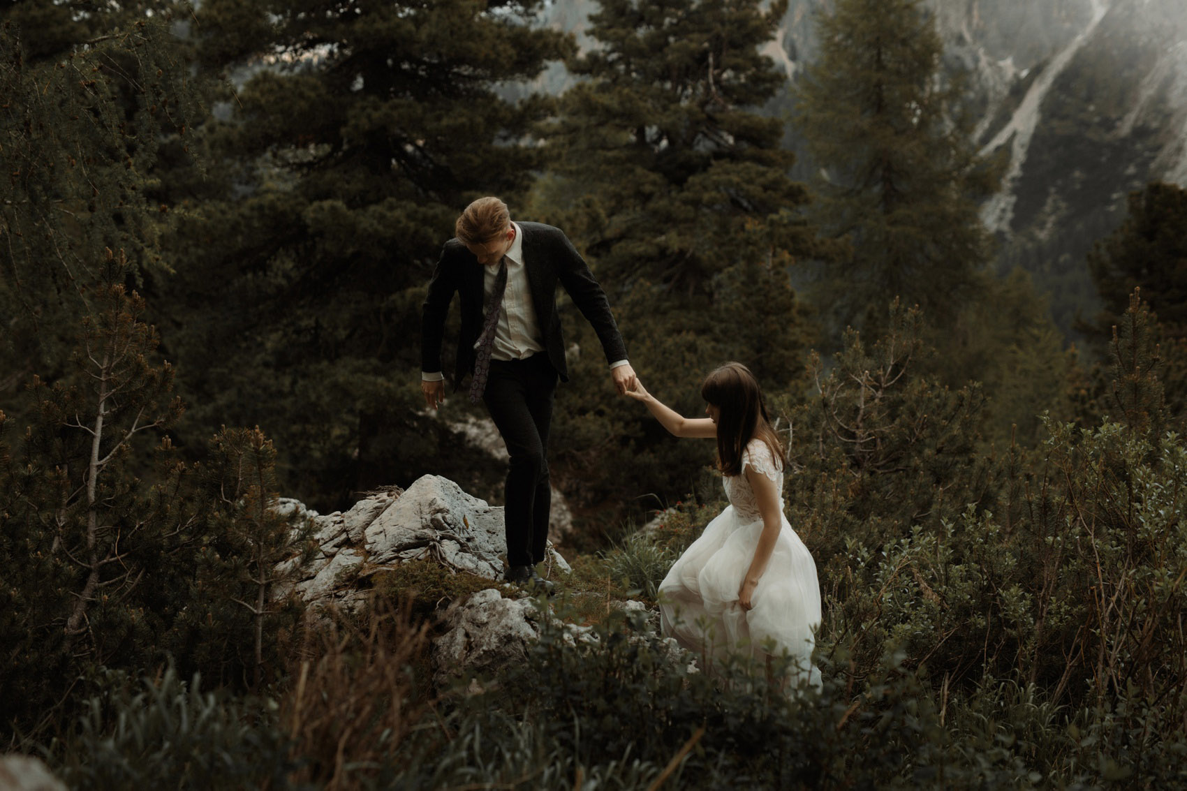 groom pulls bride on a rock
